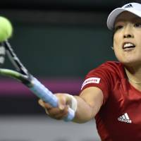 All in a day's work: Japan's Ayumi Morita hits a return against Aliaksandra Sasnovich of Belarus during their singles match on Sunday. Morita defeated Sasnovich 7-6 (7-5), 4-6, 6-4. | AFP-JIJI