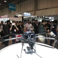 Visitors inspect one of the latest models on offer, a hexacopter, at the International Drone Expo at Makuhari Messe convention hall in Chiba Prefecture. | KAZUAKI NAGATA