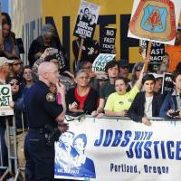 Protesters, many against granting U.S. President Barack Obama fast-track trade authority for the Trans-Pacific Partnership trade agreement, rally outside the hotel where Obama was participating in a Democratic National Committee event in Portland, Oregon, on Thursday.   REUTERS