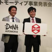 DeNA Co. executive Hiroshi Nakajima (left) and ZMP Inc. President Hisashi Taniguchi discuss the Robot Taxi project Thursday in Tokyo, their plan to launch driverless cabs in Japan. | KAZUAKI NAGATA