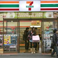 A customer exits a 7-Eleven convenience store in Tokyo in 2010. Convenience stores are undergoing a quiet shift to a higher target demographic, departing from their long-established image as a place for young shoppers. | BLOOMBERG