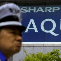 A police officer stands in front of a Sharp Corp. ad outside an electronics shop in Tokyo last month. The electronics giant's stock briefly tumbled by its daily limit of ¥80, to ¥178, on the Tokyo Stock Exchange on Monday morning, slipping below ¥200 for the first time since December 2012. | REUTERS