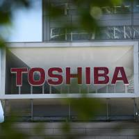 A Toshiba Corp. sign is displayed on the company's headquarters in Tokyo on Wednesday. Mired in an accounting probe, Toshiba may be removed from Japan's best-stocks index. | BLOOMBERG