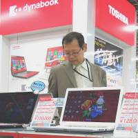 A customer checks out Toshiba laptops at an electronics shop in Tokyo on Monday. | AFP-JIJI