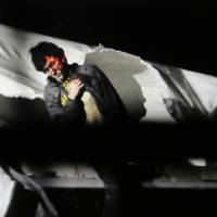 Boston Marathon bomber Dzhokhar Tsarnaev, with the red dot of a sniper rifle laser sight on his head, emerges from a boat at the time of his capture by law enforcement authorities in Watertown, Massachusetts, on April 19, 2013. On Friday, Tsarnaev was sentenced to death by lethal injection for the 2013 attack. | AP