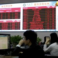 Workers monitor the carbon trading at the Beijing Environmental Exchange office on May 12.   AP