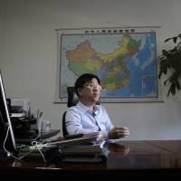 Zhou Cheng, vice president of the Beijing Environmental Exchange, speaks during an interview at his office in Beijing on May 12.   AP