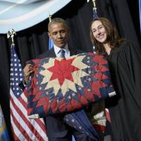 President Barack Obama holds a quilt given to him after speaking at a commencement ceremony at Lake Area Technical Institute in Watertown, South Dakota, on Friday. South Dakota was the last of the 50 states Obama has visited as president. | AFP-JIJI