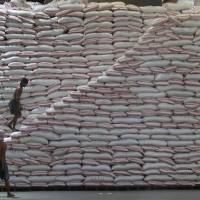 A worker walks up a pile of rice at a warehouse of the Philippines National Food Authority in Manila on Tuesday. The state grains agency continues stockpiling ahead of the lean harvest season beginning in July, aiming to keep local prices of the staple food affordable to poor Filipinos while bracing for the impact of the dry season on rice harvest. A closely watched forecast by Japan on Tuesday, and one by Australia, confirmed the El Nino weather phenomenon's return this year. | REUTERS