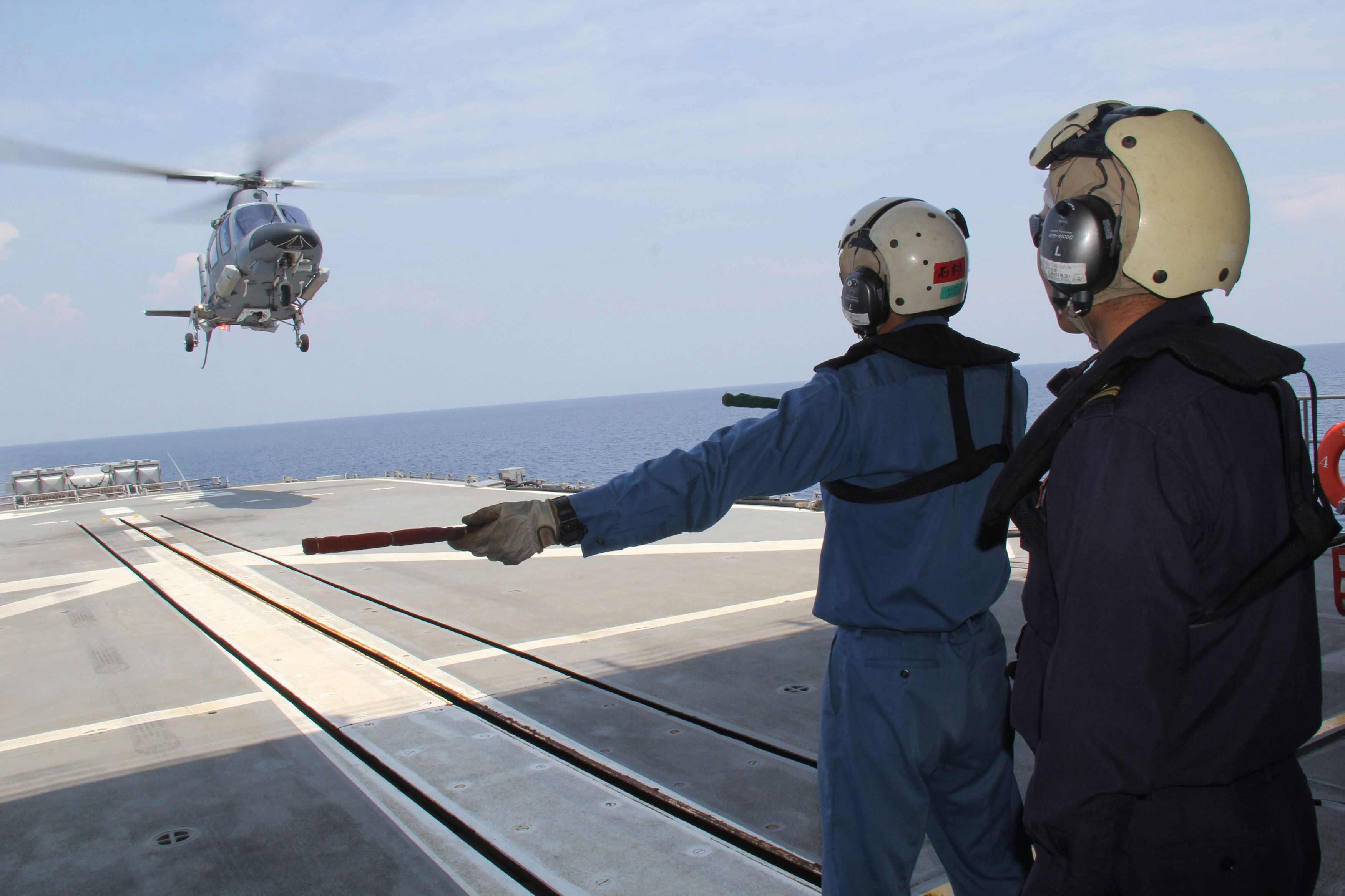 Maritime Self-Defense Force sailors guide a Philippine Navy helicopter as it lands on the deck of the destroyer Harusame during a joint naval exercise Tuesday, less than 300 km from a Philippine-claimed shoal now under Chinese control in the South China Sea. The Pentagon is considering sending U.S. military aircraft and ships to the area in an effort to assert freedom of navigation. | AFP-JIJI