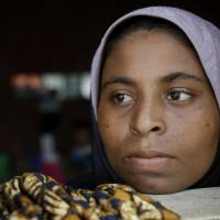 An ethnic Rohingya woman looks outside from a window at a temporary shelter in Bayeun, in Indonesisia's Aceh, on Saturday. Some of the Bangladeshis and Rohingya Muslims from Myanmar who reached Indonesia and Malaysia told harrowing tales of hardship with at sea with their traffickers.   AP