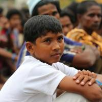 Atau Rahman sits with other Rohingya migrants at a shelter in Bayeun, Indonesia, on Friday. The 12-year-old said he had been kidnapped and held aboard a boat for weeks before the voyage.   AP