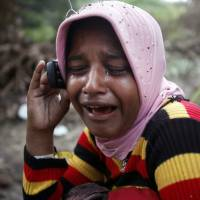 Rohingya migrant Sahiza Begum weeps as she talks on the phone Friday with her brother in Malaysia. Sahiza is at a temporary shelter in Langsa, Indonesia. 'The vulnerability of these children can never be overstated,' said Steve Hamilton, deputy chief of mission at the International Organization for Migration in Indonesia. | AP