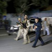 Afghan security forces arrive Wednesday at the site of an attack in Kabul. Gunmen stormed a guest house popular with foreigners just before it was due to host a concert, and up to 100 people were reportedly trapped inside as security forces fought to clear the building. | REUTERS