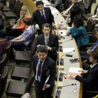 North Korean diplomats (center) leave a  panel discussion at United Nations headquarters Thursday on North Korean human rights abuses. The panel discussion briefly turned chaotic as North Korean diplomats insisted on reading a statement, amid shouts from defectors, and then stormed out of the chamber.   AP