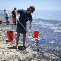 William McConnaughey, 56, (right) who drove from San Diego to volunteer, carries buckets of oil from an oil slick in bare feet along the coast of Refugio State Beach in Goleta, California, Wednesday. A pipeline ruptured along the scenic California coastline on Tuesday, spilling some 21,000 gallons (79,000 liters) of oil into the ocean and on beaches before it could be secured, a U.S. Coast Guard spokeswoman said. | REUTERS