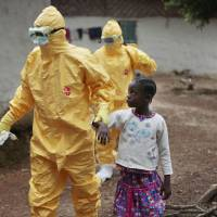 Nowa Paye, 9, is taken to an ambulance after showing signs of Ebola disease in the Liberian village of Freeman Reserve, about 50 km north of Monrovia, last Sept. 30. | AP