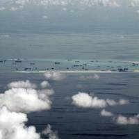 This photo taken through a  window of a military plane shows China's alleged ongoing reclamation of Mischief Reef in the Spratly Islands in the South China Sea on Monday. Gen. Gregorio Pio Catapang, the Philippines' military chief, has flown to Pagasa Island, a Filipino-occupied island in the South China Sea, amid territorial disputes in the area with China, vowing to defend the islet and help the mayor develop tourism and marine resources there. | RITCHIE B. TONGO / POOL PHOTO VIA AP