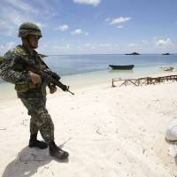 Philippine soldier Tychico Octobre patrols a beach in Pagasa Island (Thitu Island) on Monday. | RITCHIE B. TONGO / POOL / AFP-JIJI