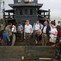 Myanmar government and U.N. officials stand on a boat used for human trafficking at a jetty outside Sittwe, Myanmar, on Saturday.  | REUTERS