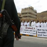 A soldier stands guard as Yemeni health workers attend a rally demanding the lifting of the blockade on Yemen, in front of the U.N. building in Sanaa on Thursday..Saudi Arabia and the United States on Thursday called for a five-day, renewable cease-fire in Yemen's war to allow aid to reach millions of civilians caught in a humanitarian crisis from the conflict. But the truce is dependent on Iran-backed rebels and their allies also agreeing to stop fighting, they said. | AP