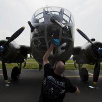 A crew member cleans the glass on a B-25 Mitchell bomber before a practice flight with other World War II-era aircraft over Culpeper Regional Airport in Brandy Station, Virginia, on Thursday. | AFP-JIJI