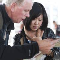 A Japanese guide helps a tourist at Kyoto Station. | ISTOCK