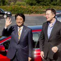 Prime Minister Shinzo Abe stands with Tesla CEO Elon Musk after undertaking a brief test ride at the carmaker's headquarters in Palo Alto, California, on Thursday. | AP