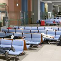 Tourists camp out at around 2 a.m. Saturday in a terminal at Kansai International Airport ahead of their early morning flight. | KYODO