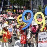 Female demonstrators march through Tokyo's Ginza shopping district on Thursday to protest a decision by the Cabinet to move ahead with reforms that would boost the Self-Defense Forces' role abroad. The placards refer to war-renouncing Article 9 of the Constitution. | KYODO