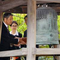 Shikataro Nakagawa and Seiko Takase, children of peace activist Chiyoji Nakagawa who donated the Peace Bell, ring the bell on Wednesday at the U.N. headquarters in New York. | KYODO