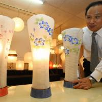 Ozeki President Morihiro Ozeki shows off 'andon' lanterns made from traditional paper and pottery crafted in the city of Gifu at his office.   CHUNICHI SHIMBUN