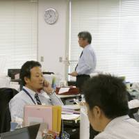 Workers at Itochu Corp. get to work earlier than usual on Oct. 1, 2013, at the trading house's offices in Minato Ward, Tokyo, to test an early-work system.   KYODO
