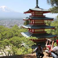Foreign tourists take photos of the five-story pagoda and Mount Fuji in Arakurayama Sengen Park in Fujiyoshida, Yamanashi Prefecture, earlier this month. | KYODO
