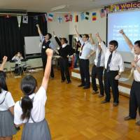 Schoolchildren in Neyagawa, Osaka Prefecture, sing with foreign teachers while taking part in an English village event hosted by the city in May 2014 at its educational center. | NEYAGAWA CITY EDUCATION TRAINING CENTER