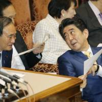 Chief Cabinet Secretary Yoshihide Suga speaks with Prime Minister Shinzo Abe during an Upper House Budget Committee meeting in March. | KYODO