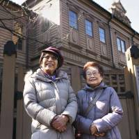 Miyuki Yashiro (left) and Yasuko, whom she adopted as a daughter after having gender reassignment surgery in 2004, pose in front of a music school where Miyuki studied before being drafted into the Imperial Japanese Army. | KYODO