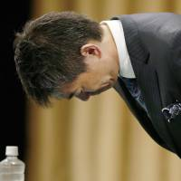 Osaka Mayor Toru Hashimoto bows at a new conference, after voters rejected a referendum proposal Sunday to merge the city into five semi-autonomous wards. | KYODO