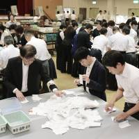 Votes are counted Sunday evening at a citizen center in Osaka's Yodogawa Ward. | KYODO