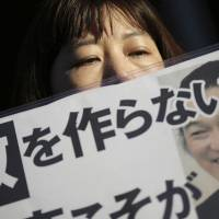 A supporter of journalist Kenji Goto holds a placard with the slogan 'Do not make an enemy' outside the Prime Minister's Official Residence in Tokyo on Feb. 1 after an online video came to light which purported to show Goto's execution. | AP