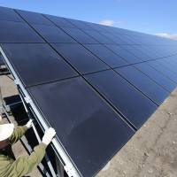 Hideki Yoshida, an electrical engineer at Japan Asia Group Ltd., inspects solar panels at the Kushiro Hoshigaura SolarWay solar photovoltaic power plant run by unit Kokusai Kogyo Holdings Co. in Kushiro, Hokkaido, in May 2013. | BLOOMBERG