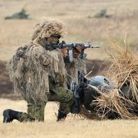 A Ground Self-Defense Force soldier takes aim during a drill in Narashino, Chiba Prefecture, in January 2014. The public is uneasy about the wording of two security bills that would allow Japan's troops to use force abroad for the first time since the war. | AFP-JIJI