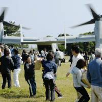 Participants taking part in a tsunami disaster drill unload imitation boxes of relief supplies from an Osprey tilt-rotor aircraft in Kushimoto, Wakayama Prefecture, last October. | KYODO