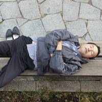A man sleeps on a bench in Tokyo in November 2010. | ISTOCK