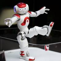 Aldebaran Robotics demonstrates its Nao robot, which offers basic information about banking services in Japanese, English and Chinese, at a branch of the Bank of Tokyo-Mitsubishi UFJ in Tokyo in April. | REUTERS