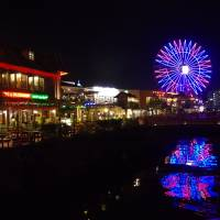 Bright lights illuminate the American Village shopping area of Chatan, Okinawa Prefecture, on May 10. The now-thriving area, built on a former U.S. military site, is one of the most successful redevelopment projects in Okinawa. | REIJI YOSHIDA