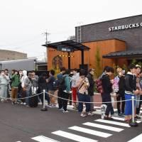 People wait for a Starbucks outlet to open Saturday in Tottori, the last prefecture in the nation to become part of the coffee giant's network. | KYODO