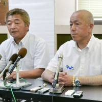 Local fisheries cooperative executives Shuichi Matsumoto (left) and Yoshifumi Kai speak to the media during a news conference on Wednesday in Taiji, Wakayama Prefecture, about their plan to continue dolphin hunting. | KYODO