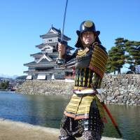 Chris Glenn poses in traditional battle armor he handcrafted, in front of Matsumoto Castle in Nagano Prefecture. | COURTESY OF CHRIS GLENN