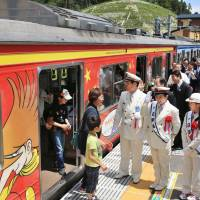 Railway workers greet passengers at Nobiru Station in Miyagi Prefecture on Saturday morning as the JR Senseki Line line resumed full services more than four years after being washed away by the tsunami of March 11, 2011. | KYODO